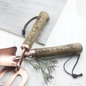 "Download Product Image Personalised Luxe Copper Trowel and Fork Set Product Specification Length: 6cm Width: 33cm Height: 6.5cm Product Description Gardening couldn't get any more chic with this luxe trowel and fork set. A gardening set which is finally as beautiful to look at as it is to use. Make light work of those gardening tasks with the solid ash handles which are designed with a slight curve for extra comfort. Copper has been favoured by gardeners for many years for its benefits for improving soil. The trowel has been marked in centimetres and inches so planting at the correct depth has never been easier. High quality copper-plated carbon steel Solid ash handles Leather hooks for hanging Trowel scoop marked in centimetres and inches up to 10cm/4"" Personalised Luxe Copper Trowel and Fork Set"